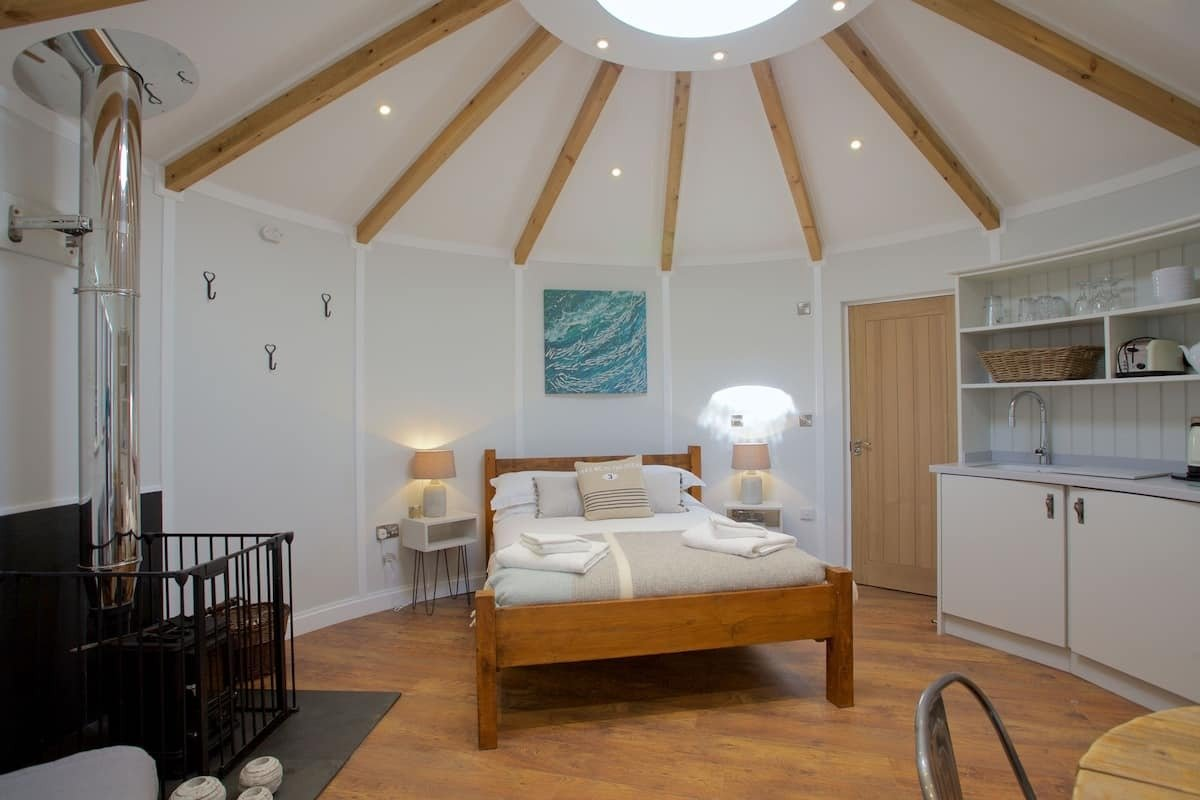 bed-kitchen-and-wood-burner-inside-the-ocean-room-roundhouse