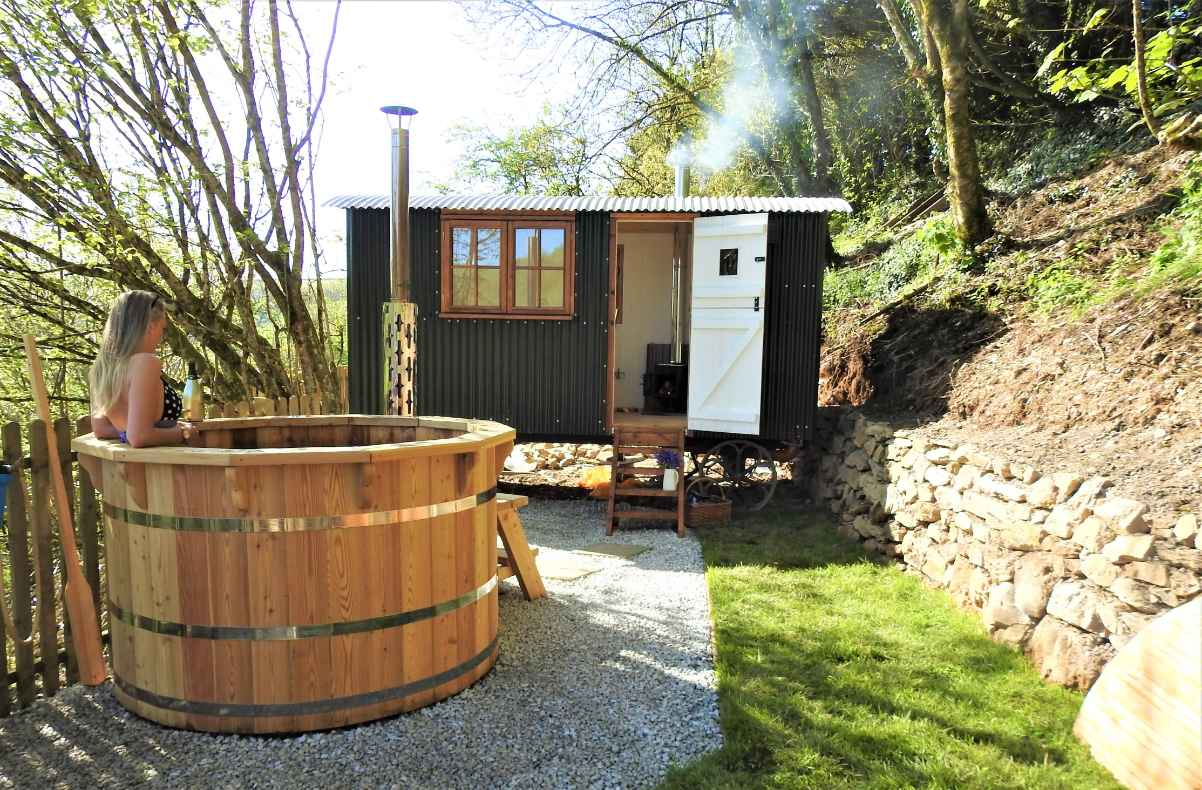 blonde-woman-in-woodfired-hot-tub-by-eileen-shepherds-hut-glamping-with-hot-tub-cornwall