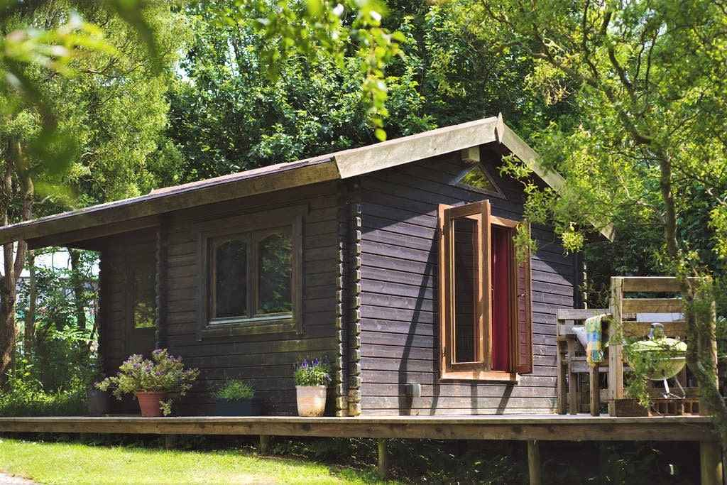 cosy-orchard-cabin-on-decking-with-trees-behind