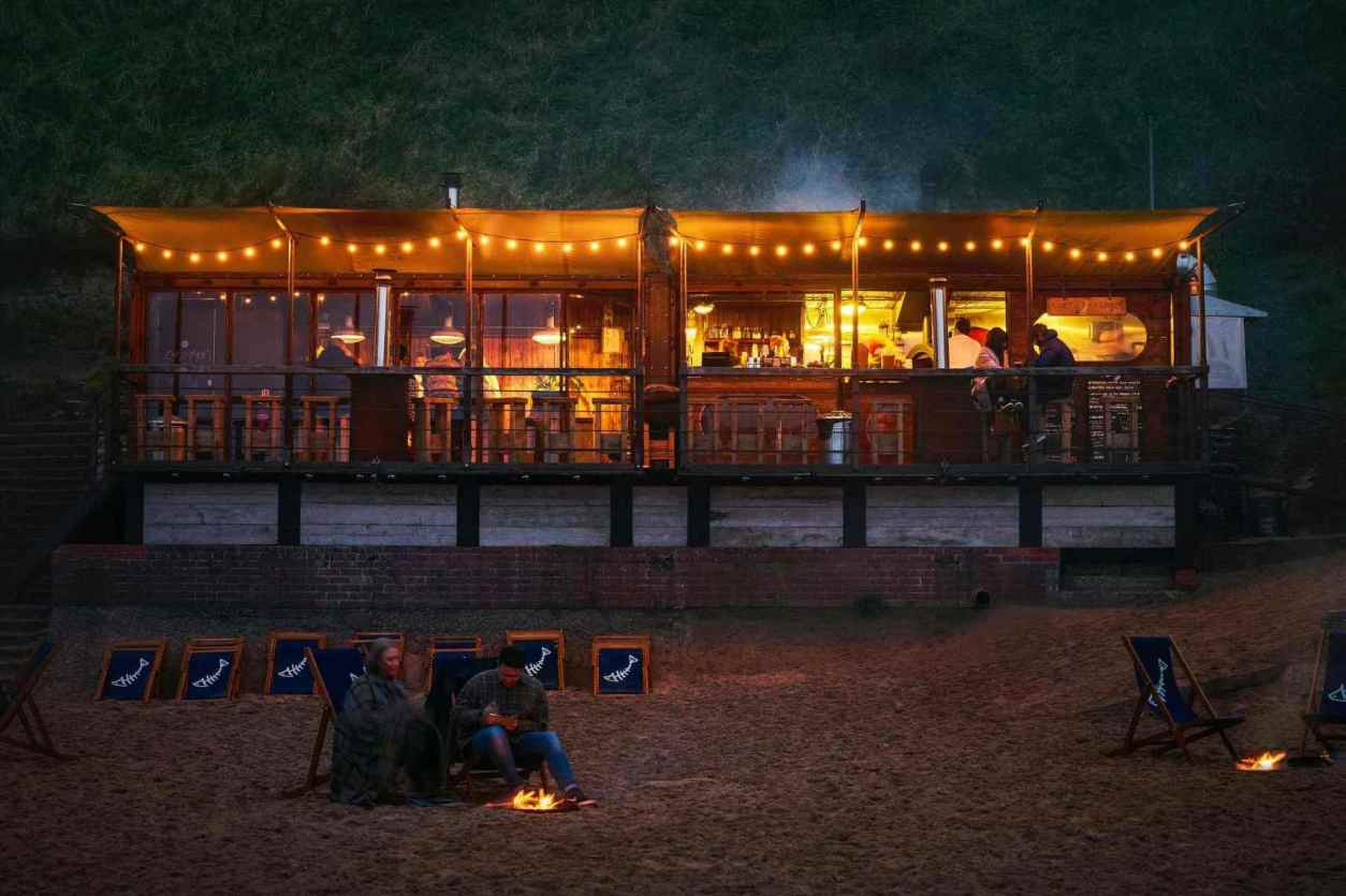 couple-sat-on-beach-by-fire-at-rileys-fish-shack-at-night