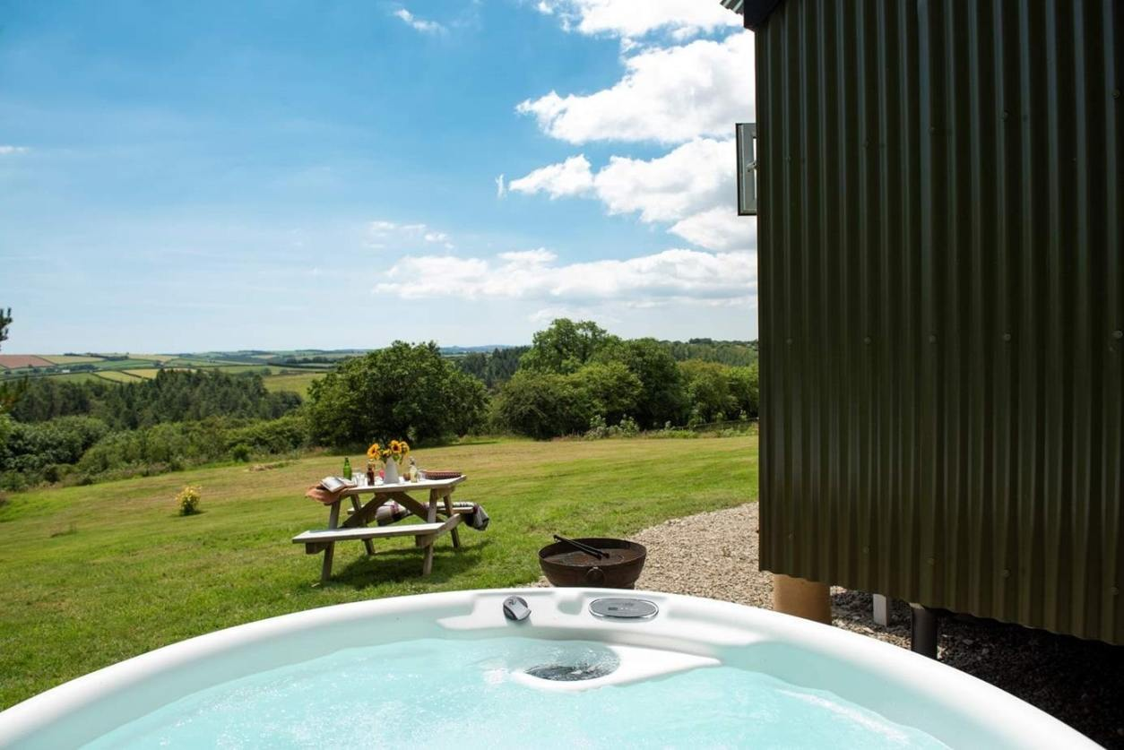 hot-tub-and-picnic-table-outside-the-enchanted-wardrobe-shepherds-hut-glamping-with-hot-tub-cornwall