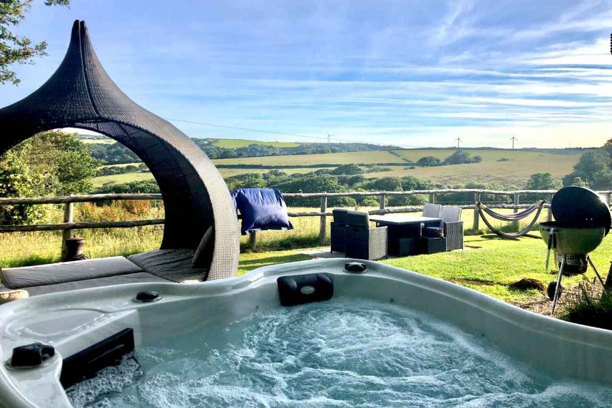 hot-tub-day-bed-and-outdoor-furniture-in-field-at-rosies-retreat-shepherds-hut-glamping-with-hot-tub-cornwall