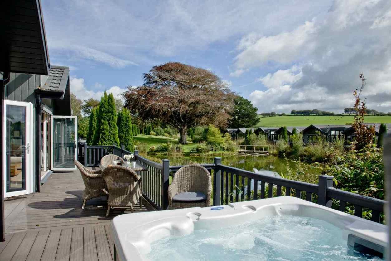hot-tub-on-decking-of-kentisbury-grange-lodges-overlooking-lake-lodges-with-hot-tubs-devon