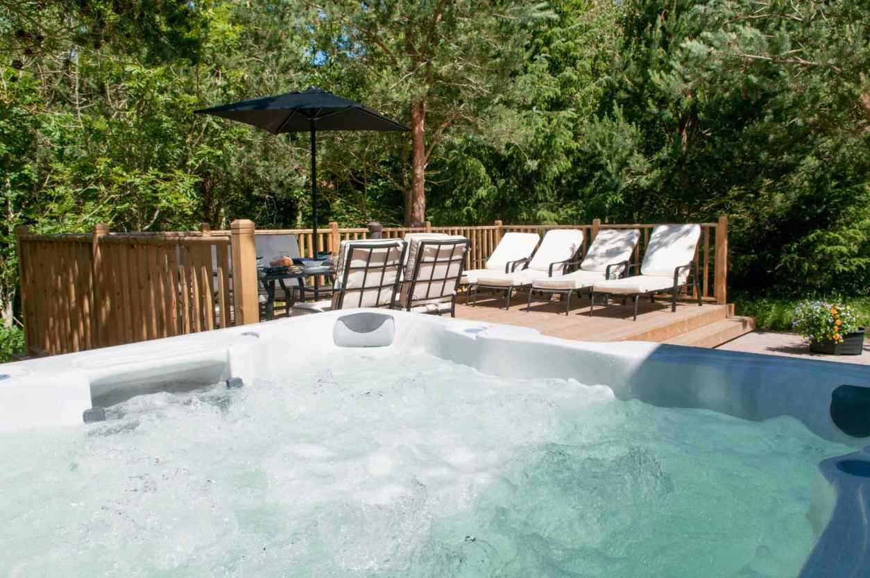 outdoor-hot-tub-garden-furniture-and-sun-loungers-on-decking-at-the-getaway