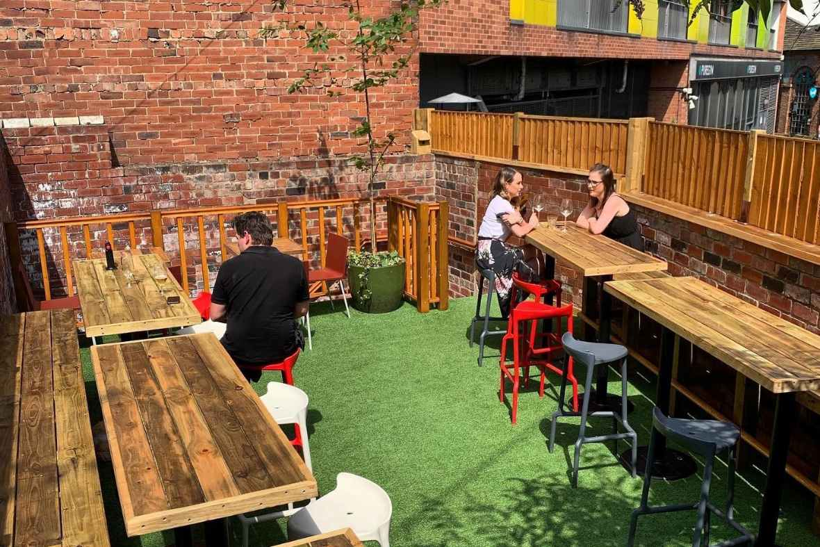 people-sitting-at-picnic-tables-drinking-on-rolands-sun-terrace