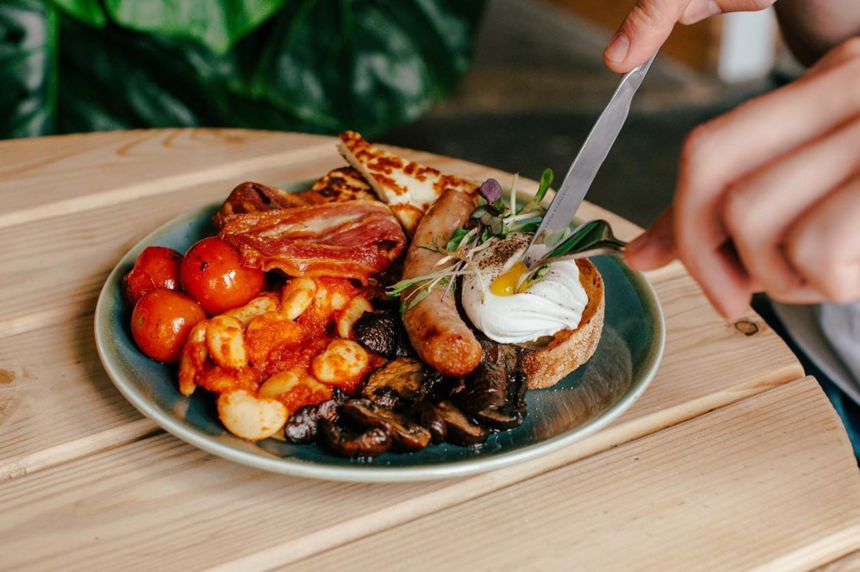 person-tucking-into-vegetarian-breakfast-at-sheaf-st-vegan-restaurants-leeds