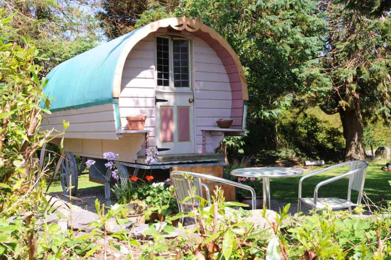 pink-chez-shea-gypsy-wagon-with-outdoor-seating-in-field-glamping-kerry