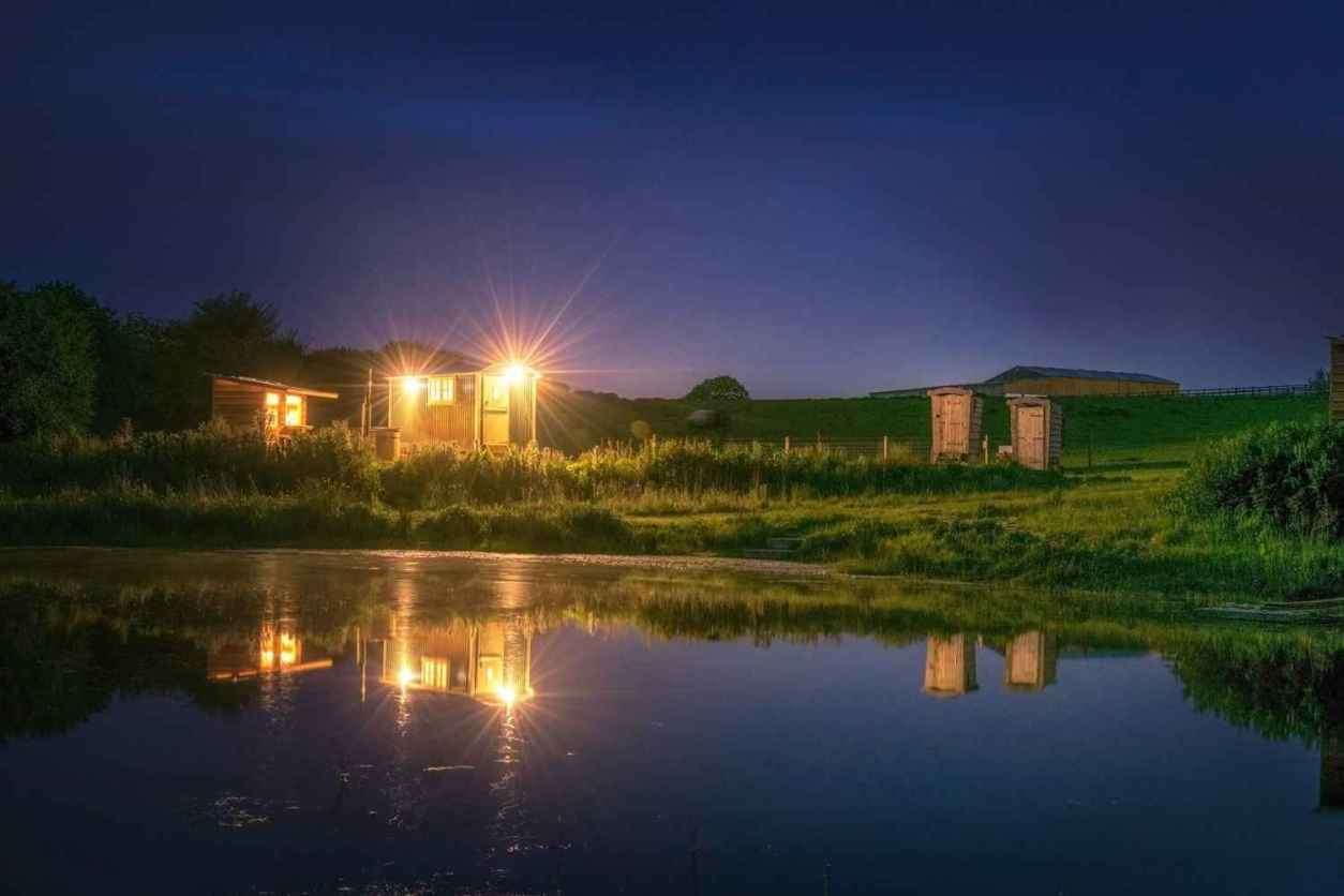 shepherds-hut-in-field-by-lake-lit-up-at-night-glamping-with-hot-tub-cornwall