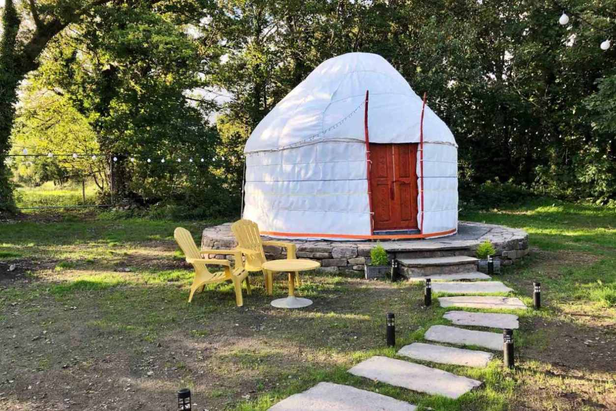 stepping-stones-leading-to-white-mongolian-yurt-in-field-glamping-kerry