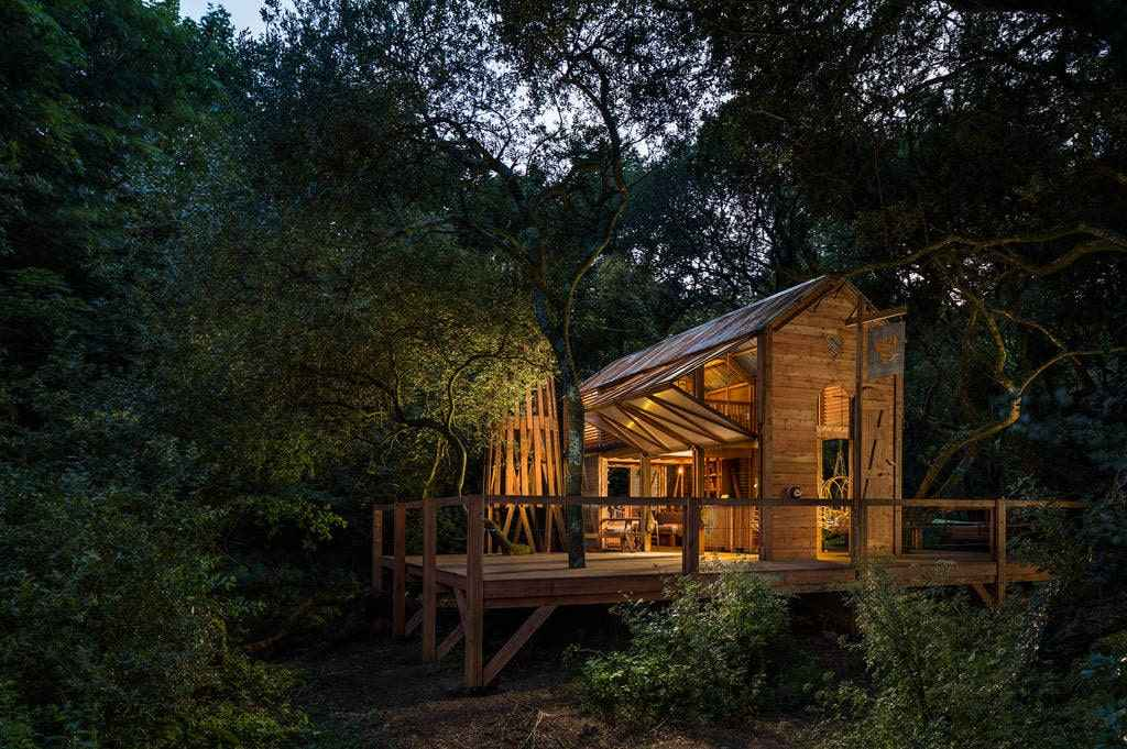 the-danish-cabin-lit-up-in-the-evening-in-woodland-at-kudhva-glamping-with-hot-tub-cornwall