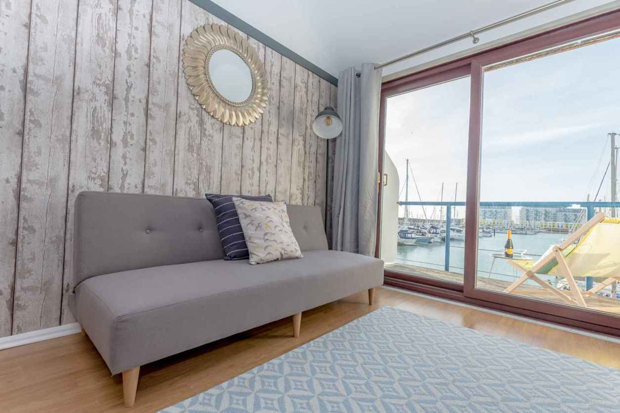 the-harbour-hut-living-area-with-balcony-overlooking-harbour