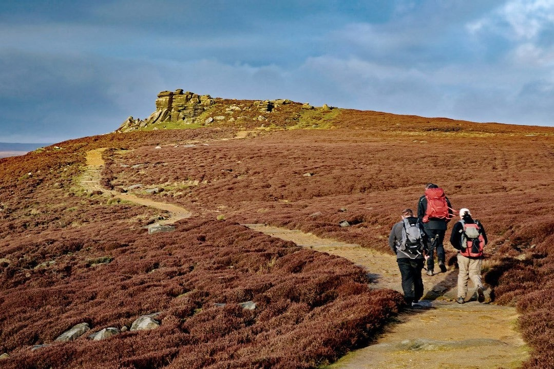 three-hikers-walking-up-to-hurkling-stones