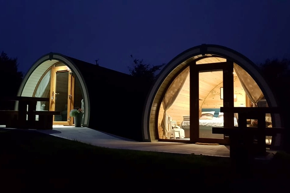 two-eyeries-glamping-pods-lit-up-at-night