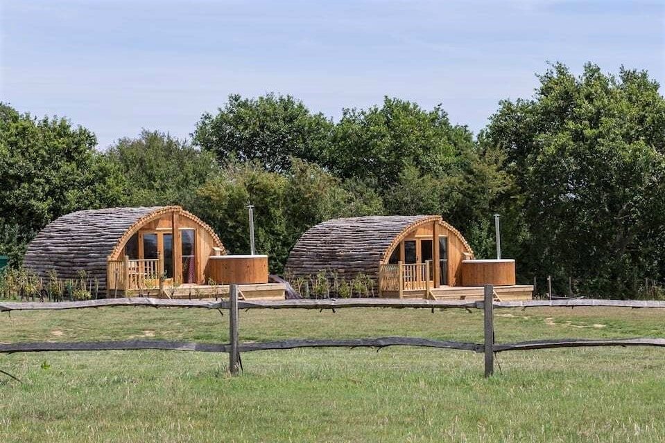 two-log-cabins-with-wood-fired-hot-tubs-in-field