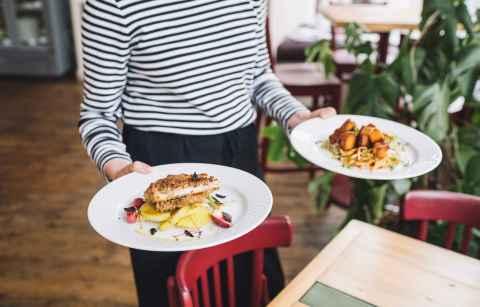waitress-serving-two-plates-of-food-at-eat-your-greens-vegan-restaurants-leeds