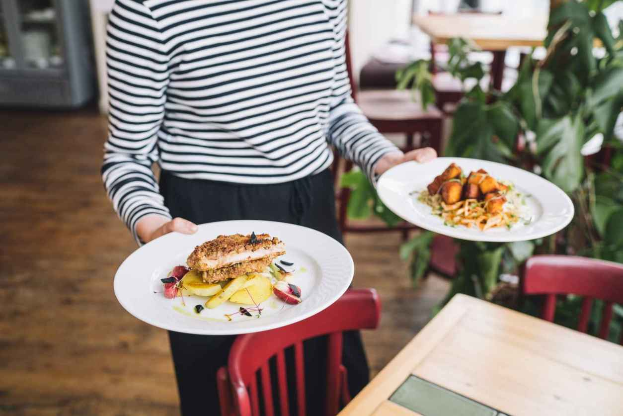 waitress-serving-two-plates-of-food-at-eat-your-greens-vegan-restaurants-leeds