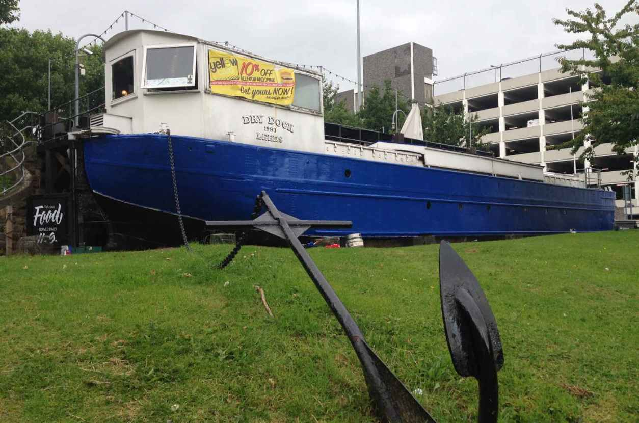 white-and-blue-dry-dock-boat-on-grass