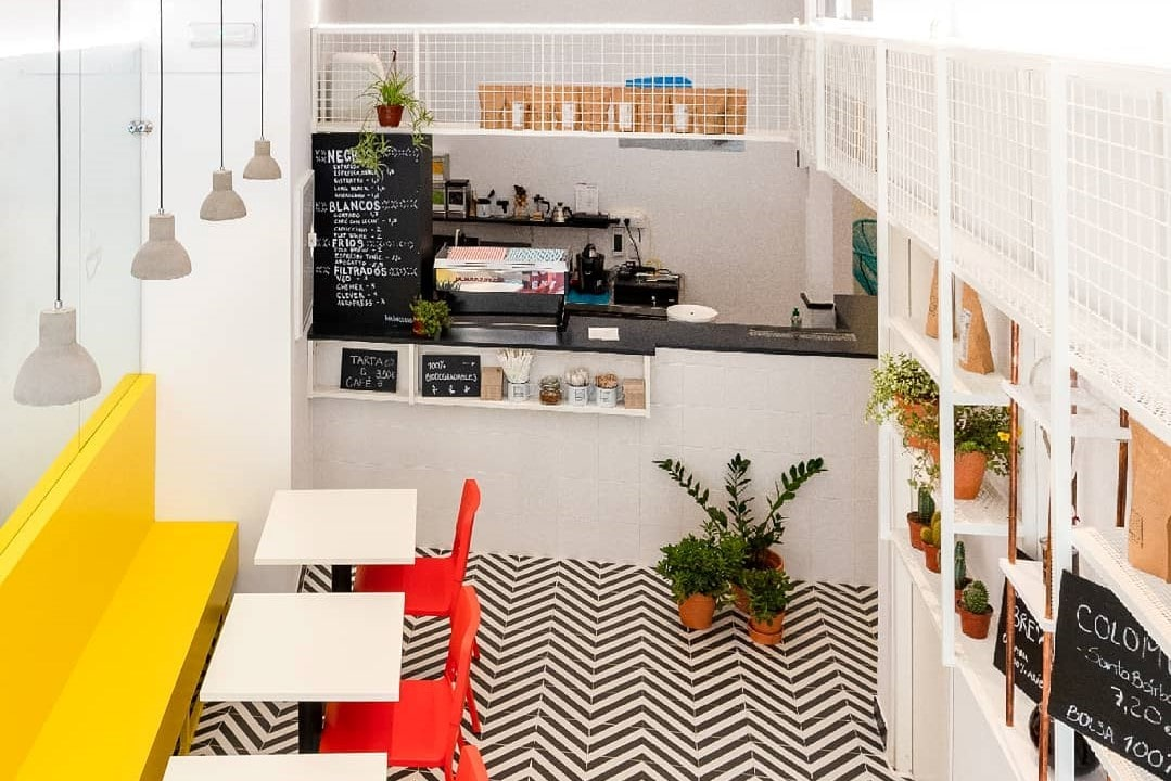 white-interior-of-parceria-cafe-with-red-and-yellow-seating