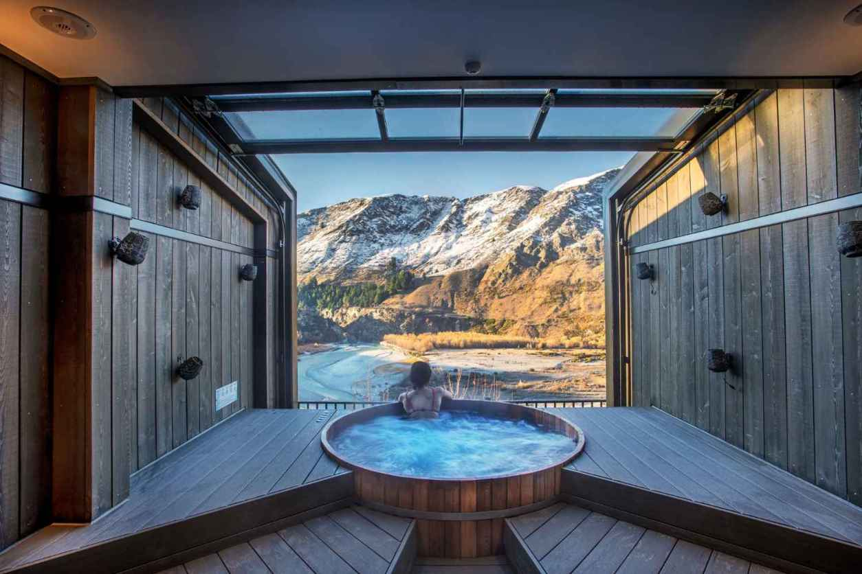 women-in-outdoor-hot-tub-overlooking-mountains-at-onsen-hot-pools-things-to-do-in-queenstown-in-winter