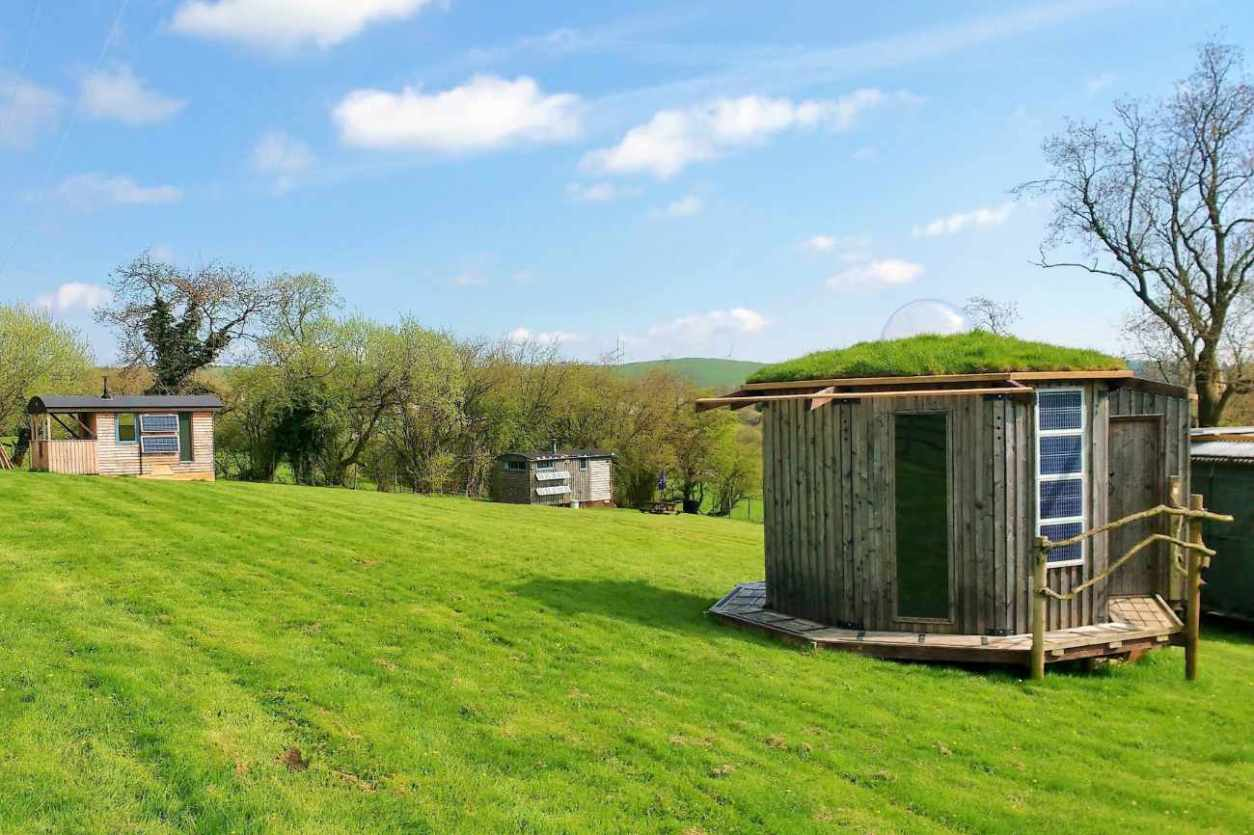 ecopod-holidays-huts-in-field-on-sunny-day