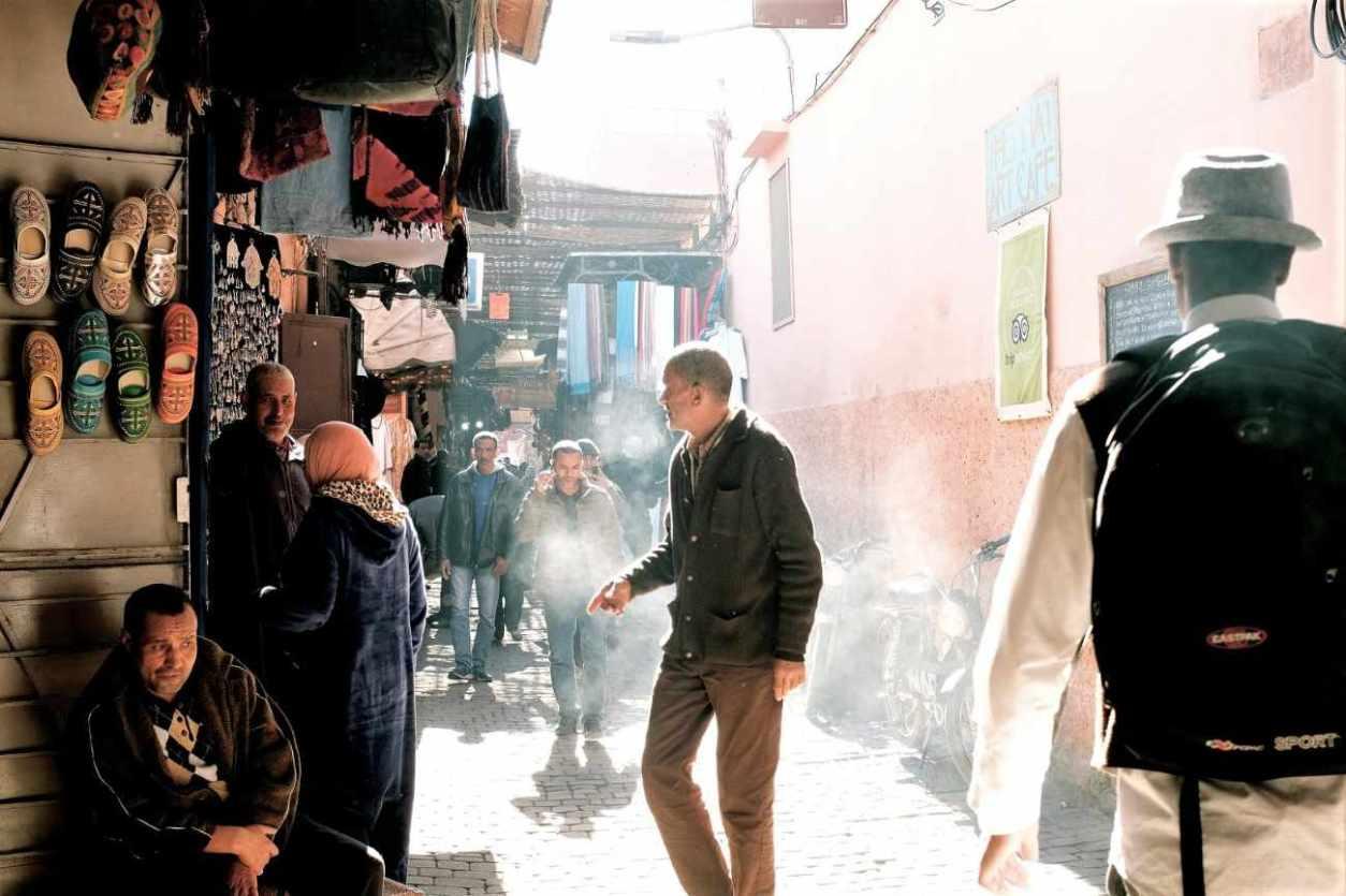 people-walking-down-smokey-alleyway-in-marketplace