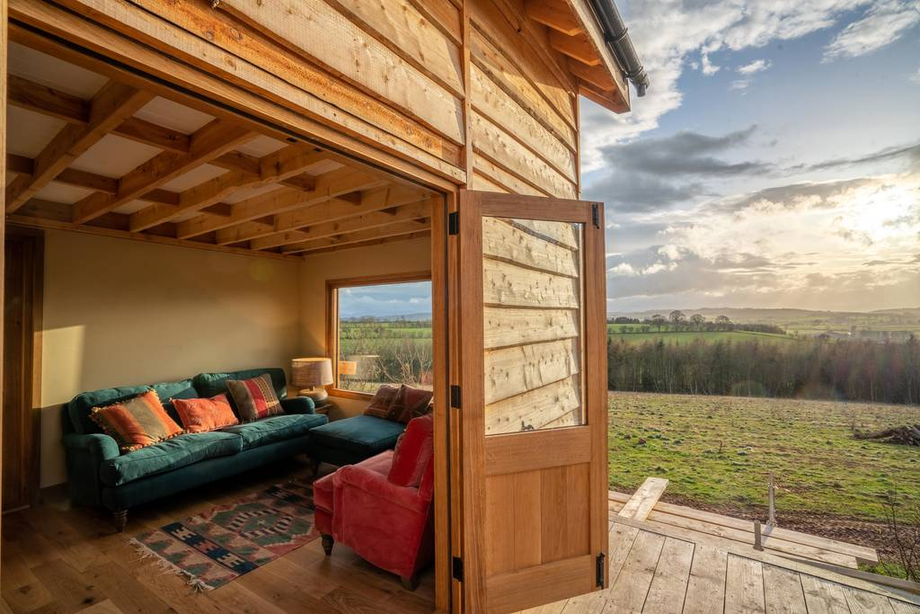 silva-treehouse-living-area-overlooking-field-at-into-the-woods