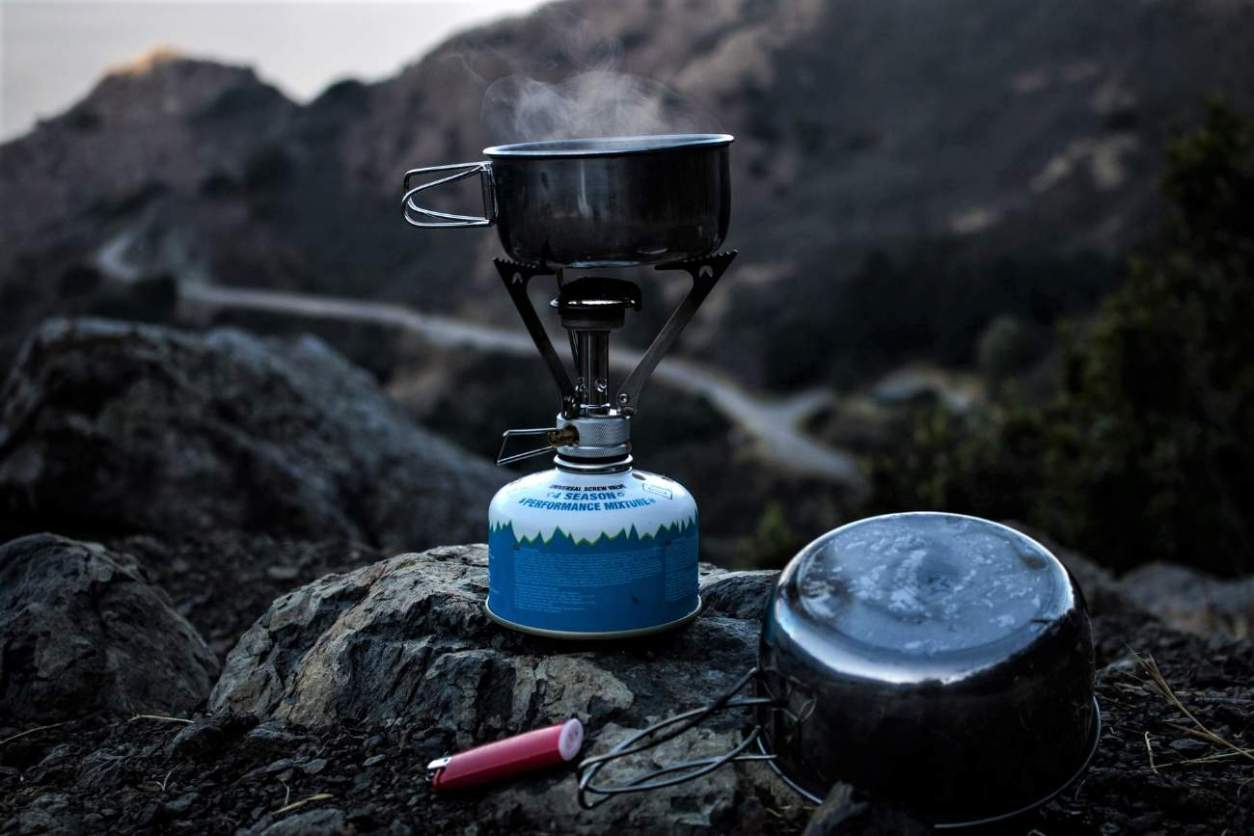 camp-stove-cooking-food-on-rock