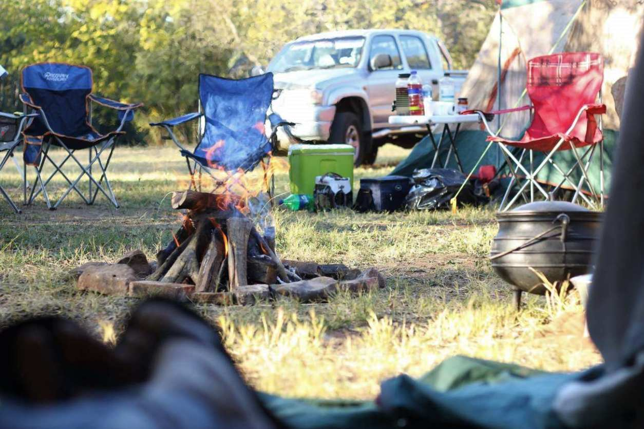 camping-chairs-around-campfire-by-tents-road-trip-packing-list