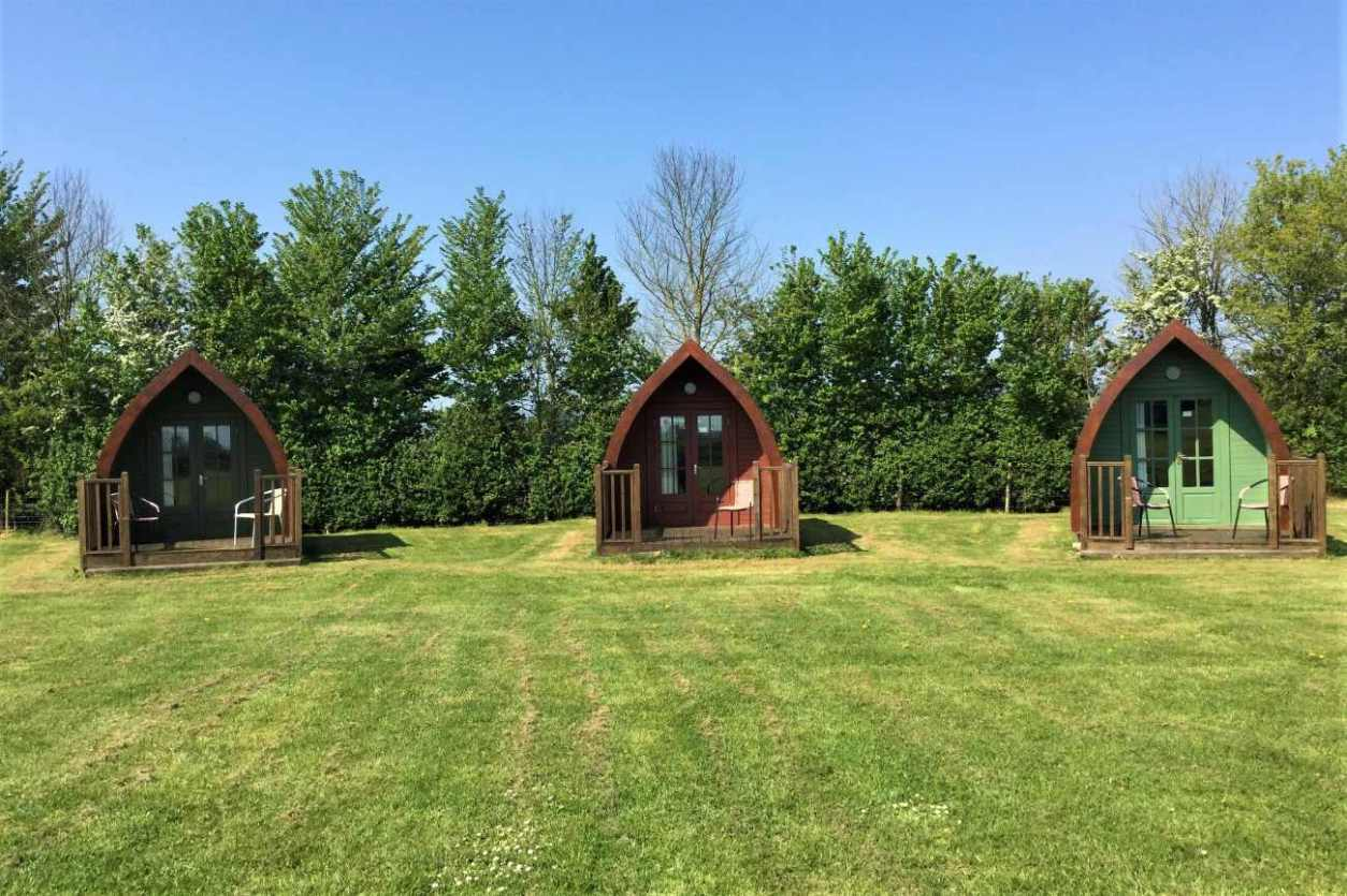 three-glamping-pods-in-field-at-apple-orchard