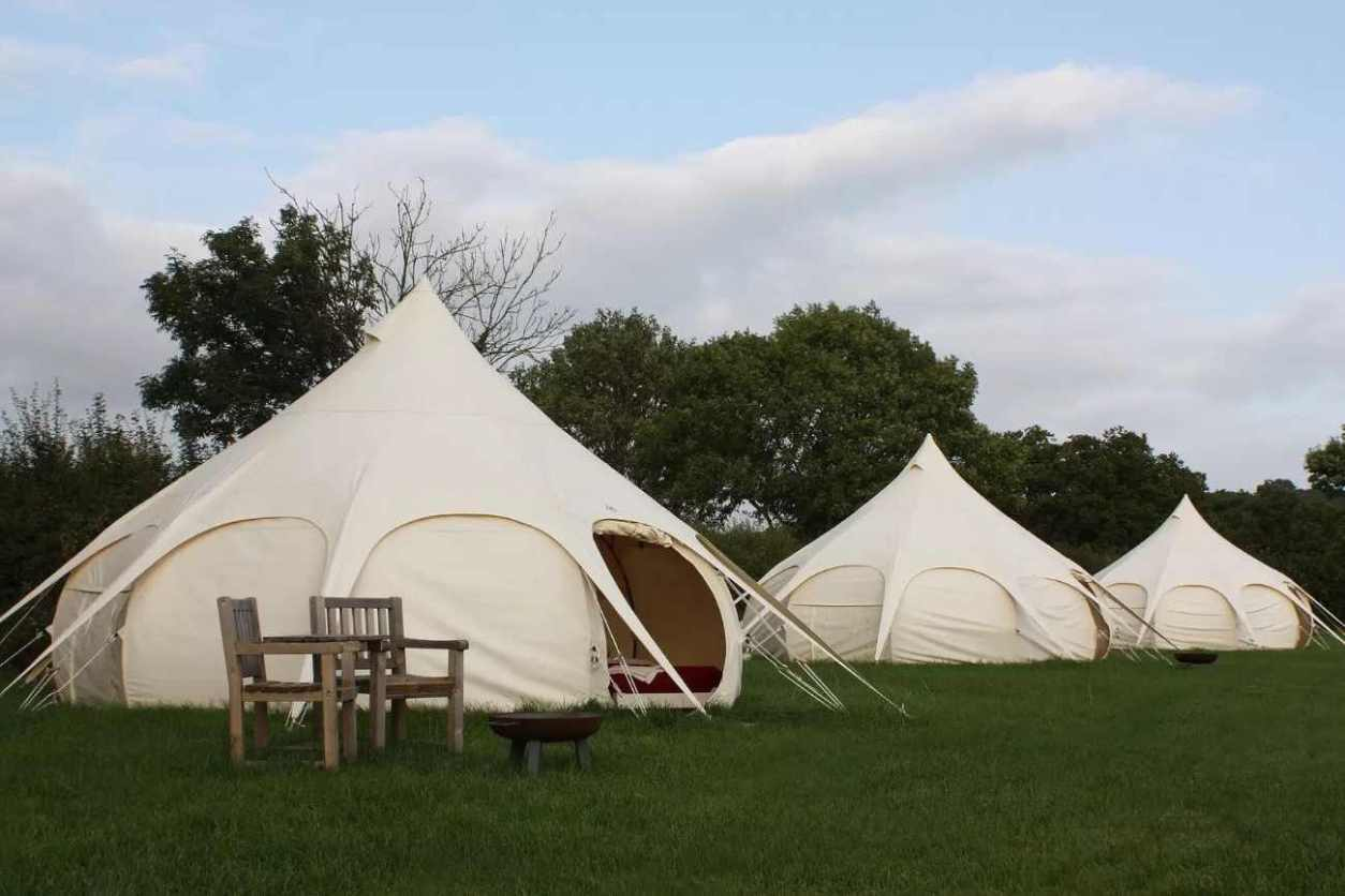 three-white-cotswold-meadow-bell-tents-in-field