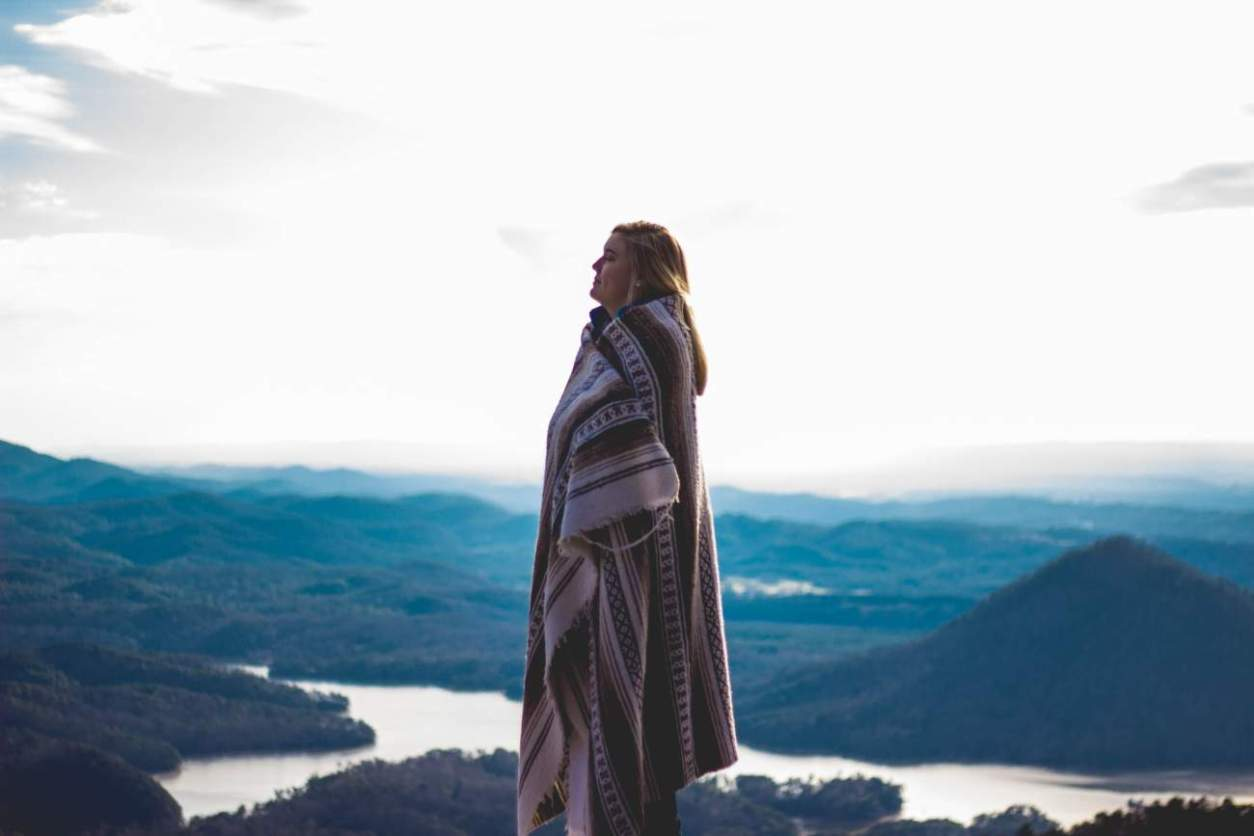 woman-wrapped-in-blanket-at-sunset-on-mountain