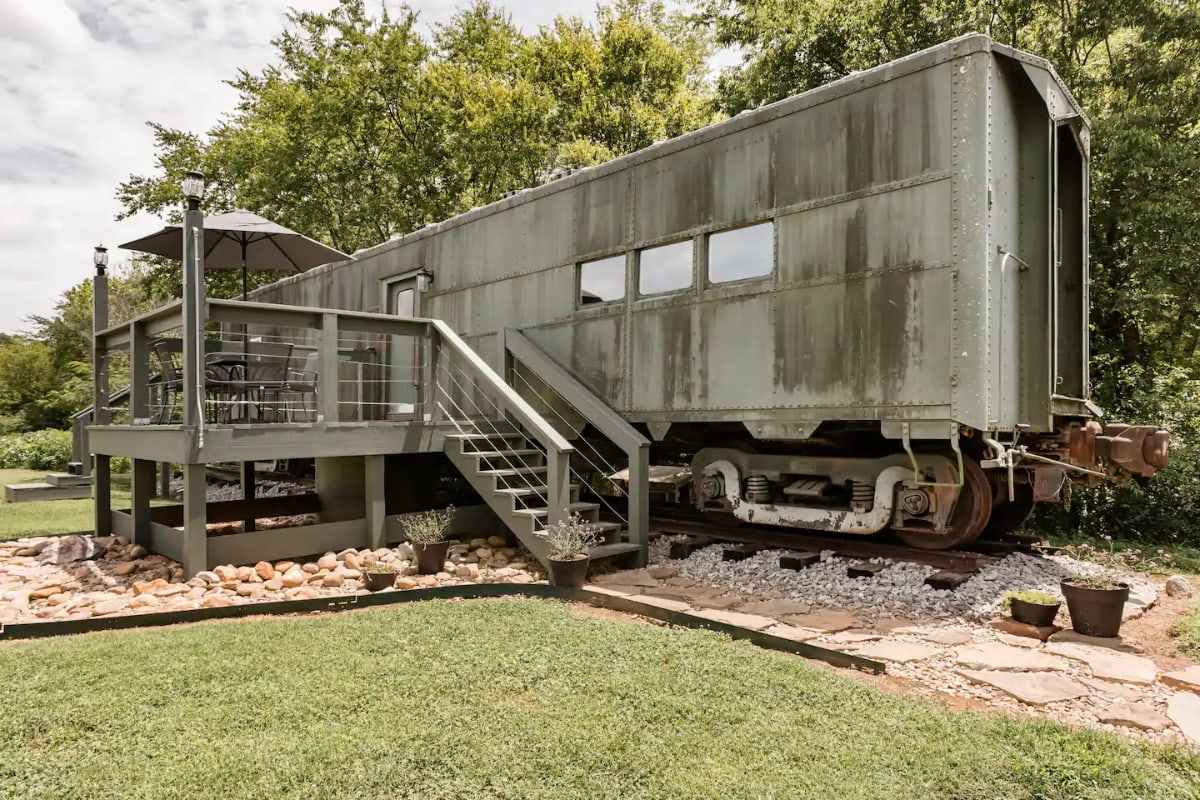 converted-WWII-train-car-with-decking-in-field