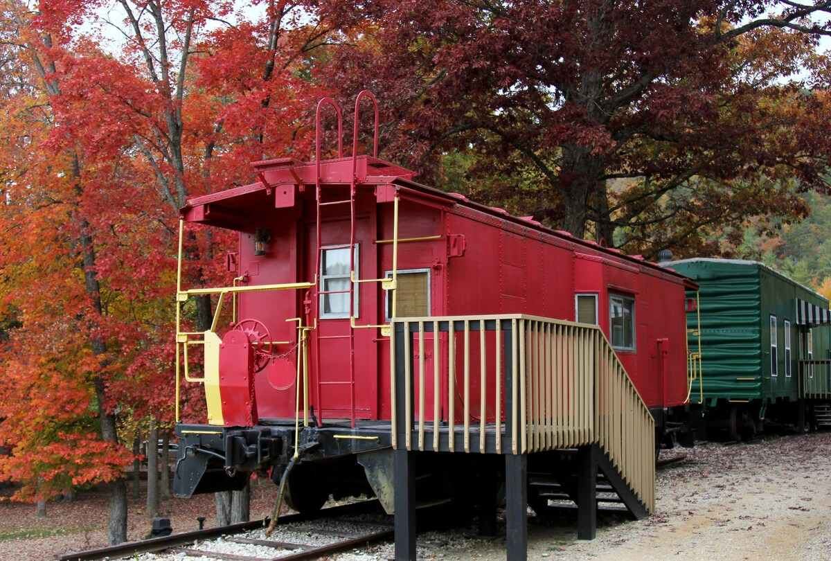 cozy-red-caboose-beside-trees-in-fall