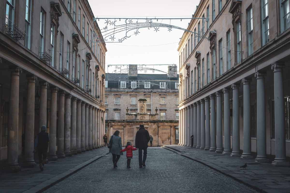 couple-and-child-walking-down-bath-street-in-winter