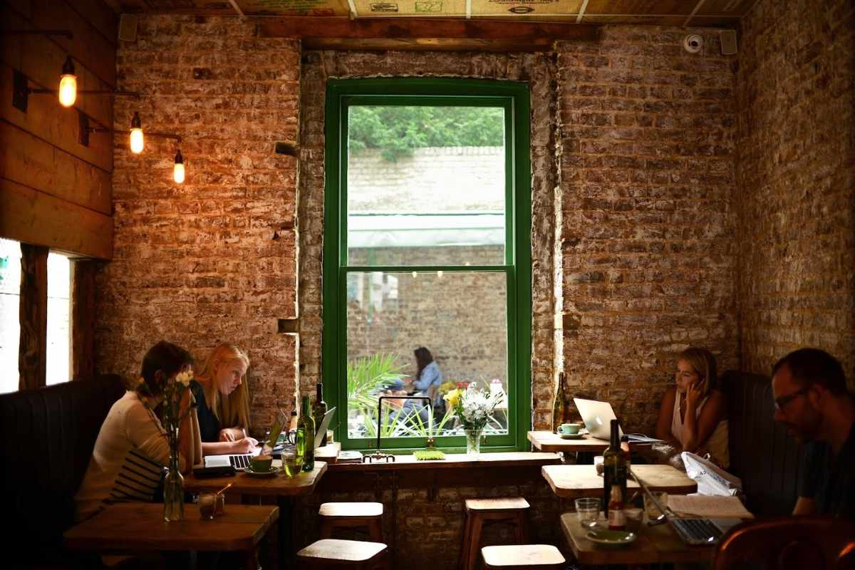 people-eating-on-tables-by-brick-wall-at-brickwood-cafe