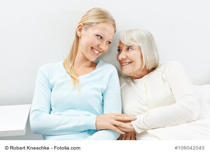 Junge Frau und Seniorin lächeln sich glücklich an