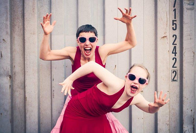 Tänzerinnen Nele und Corinna tragen knallrote Kleider und dunkle Sonnenbrillen, schauen in die Kamera und reißen den Mund auf.