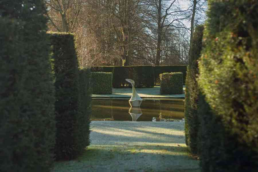 The Pond Garden: Formal pool surrounded by hedge of Taxus Baccata. Sculpture of White