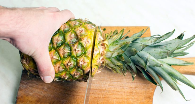 cutting the top off a pineapple