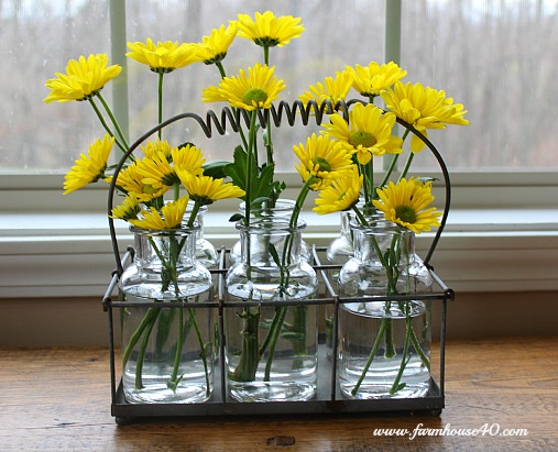 yellow daisies in glass bottles
