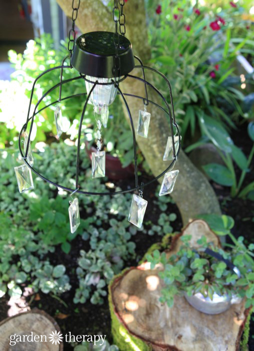 DIY-Solar-Light-Chandelier-hanging-over-rustic-tree-stump-table-and-chairs