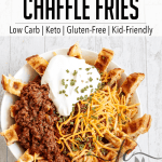 "Chow down on these Low Carb, Keto Chili Cheese Chaffle Fries when you're craving some real comfort food. Perfectly firm and crispy chaffles are sliced into ""fries,"" piled with meaty, beanless chili and topped with cheddar cheese, a hefty dollop of sour cream and a sprinkling of vibrant, flavorful chives."