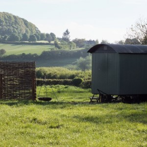 The view of a green shepherd hut with rural scene beyond