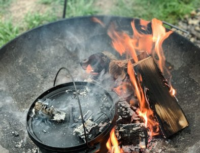 A dutch oven is cooking on a burning fire pit