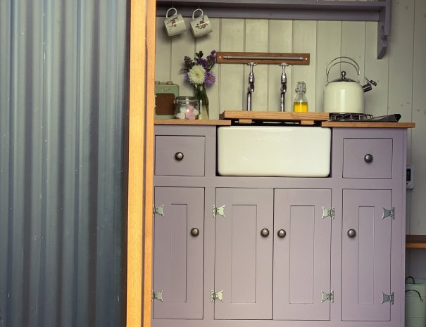 Looking through the oak door of the Happy Hare there is a lovely purple kitchen with Belfast sink and gas hob