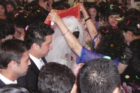 The grooms mother lifts the bride's veil at a Uyghur wedding