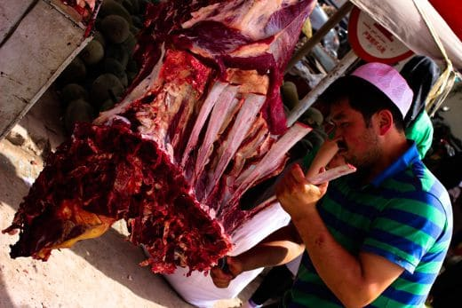 A butcher fixes meat in Kashgar's Sunday Market