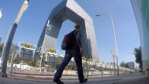 Josh from FarWestChina walks past the CCTV Tower in Beijing, China