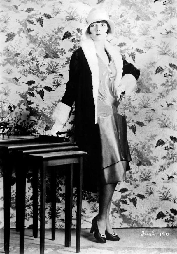 Mulher posando com vestido e chapéu dos anos 20