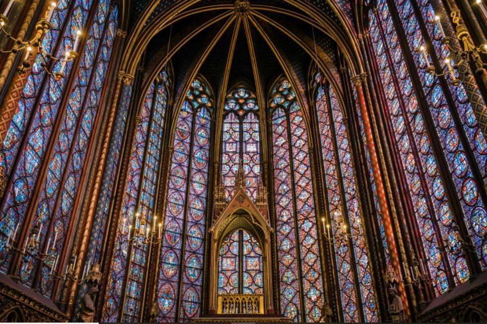 Foto de parte do Interior da igreja Sainte Chapelle, na França, one se vê a arquitetura gótica com mosaicos, abóboda e arcos